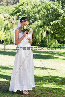 Bride smelling flowers in park