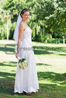 Bride holding flower bouquet in park