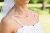 Closeup of bride wearing necklace in garden