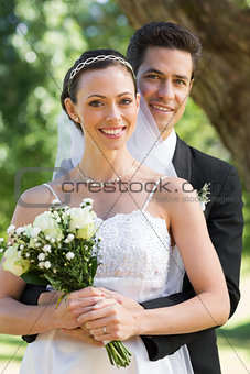 Groom embracing bride from behind in garden