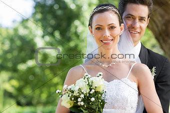 Smiling bride and groom in garden