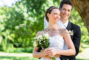 Groom and bride standing in garden