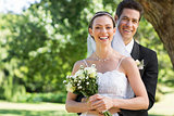 Newly wed couple with flower bouquet in park