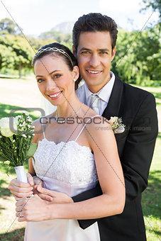 Groom hugging bride from behind in park