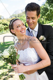Bride with flower bouquet looking at man in park