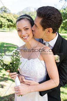 Groom kissing bride on cheek in garden