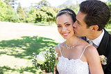 Groom kissing beautiful bride on cheek in garden