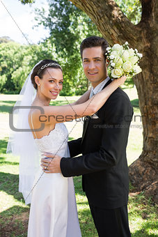 Bride and groom embracing in garden
