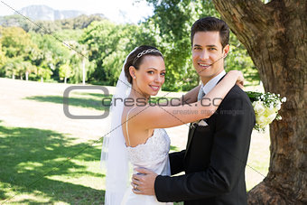 Smiling bride and groom embracing in garden