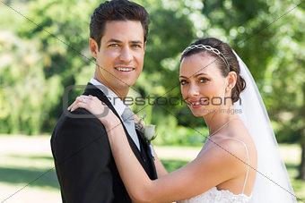 Bride and groom smiling in garden