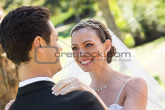 Bride looking at groom in garden