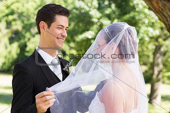 Groom unveiling his bride in garden