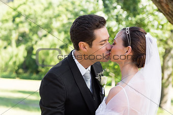 Bride and groom kissing each other in garden