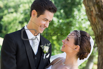 Bride and groom looking at each other in garden