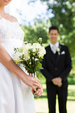 Bride holding bouquet with groom standing in background