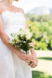 Midsection of bride holding bouquet in garden