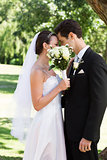 Loving couple kissing behind bouquet in garden
