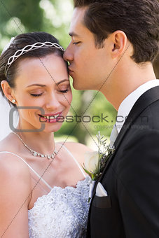 Groom kissing bride on head in garden