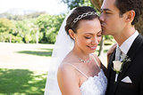 Groom kissing shy bride on head in garden