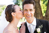 Bride kissing groom on cheek in garden