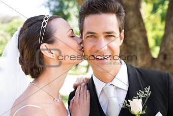 Bride kissing groom on cheek in garden