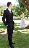 Groom looking at bride in garden
