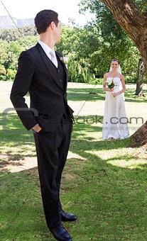 Groom looking at bride in garden