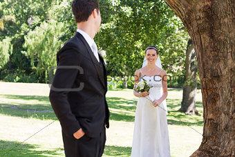 Bride looking at groom in garden