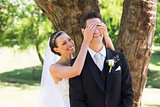 Bride covering eyes of groom in garden