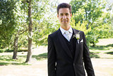 Confident groom smiling in garden