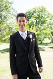 Groom in tuxedo standing at garden