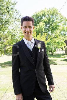 Groom in tuxedo standing at garden