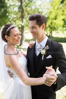 Bride and groom dancing while holding hands
