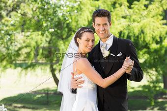 Smiling bride and groom dancing in garden