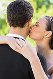 Closeup of bride kissing groom on cheek