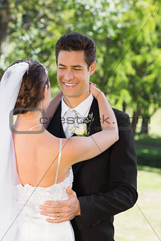 Smart groom embracing woman in garden