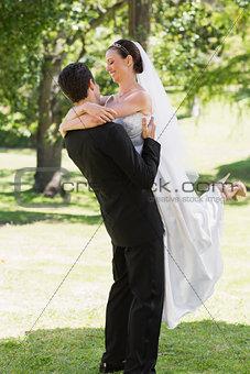 Groom lifting bride in garden