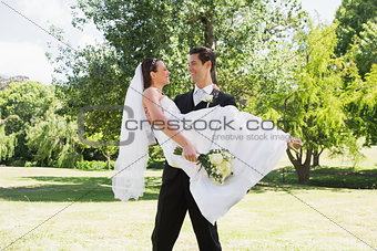 Groom carrying bride in arms at garden
