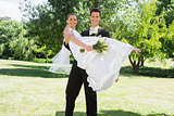 Young groom lifting bride in arms at garden
