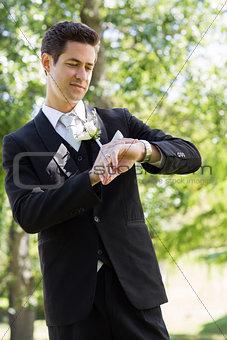 Bridegroom checking time in garden