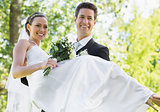Groom carrying bride in garden