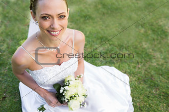 Bride holding flower bouquet while sitting in garden