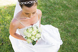 Bride holding bouquet while sitting on grass