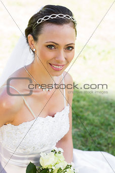 Bride sitting on grass in garden