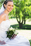 Bride holding bouquet while sitting in garden