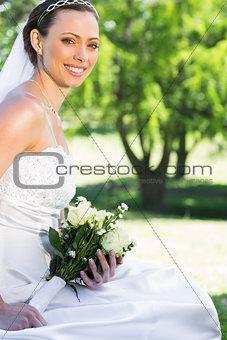 Bride holding bouquet while sitting in garden