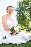 Confident bride holding bouquet in garden