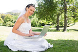 Beautiful bride using laptop in garden