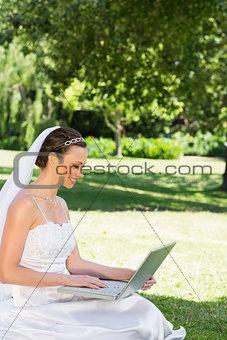 Bride using laptop on grass at garden