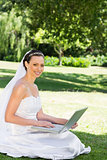 Beautiful bride with laptop sitting on grass